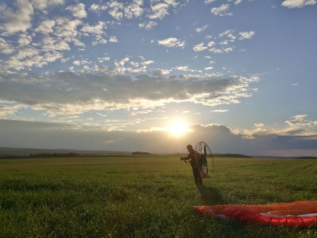 HuaweiP9 Motorparagliding Green Color Grass Field Beauty In Nature Sky Sunlight Sunset Day Outdoors Nature Adult Landscape One Person One Man Only No Filter Cloud - Sky Lifestyles Men