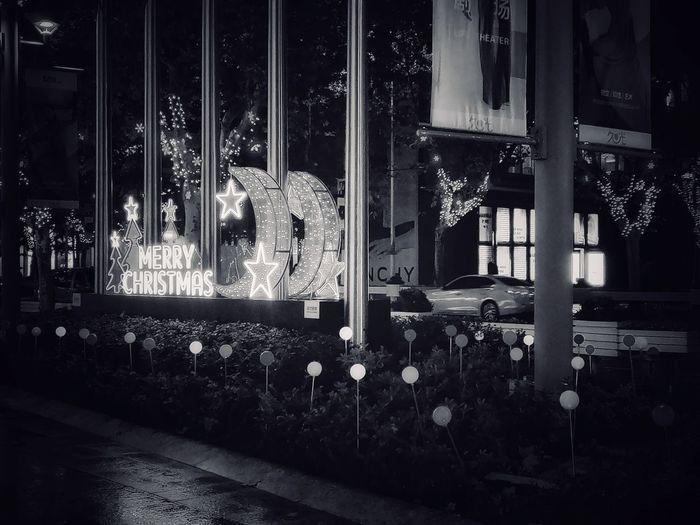 Illuminated lanterns hanging by window at night