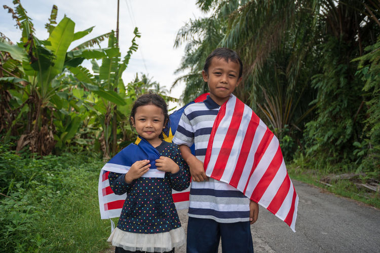 Portrait Of Siblings Holding Malaysian Flag While Standing On Road Amidst Plants