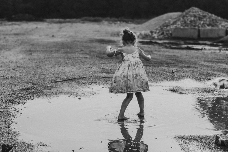 Water Full Length One Person Childhood Girls Real People Leisure Activity Land Lifestyles Standing Reflection Outdoors Nature Child barefoot Puddle Springtime