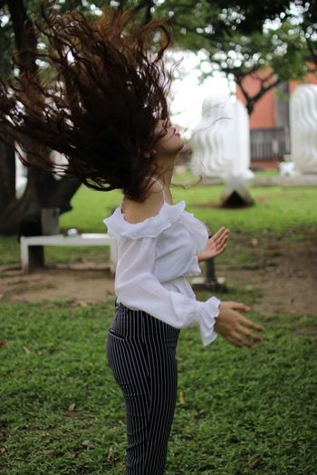 Side view of woman tossing hair while standing at park