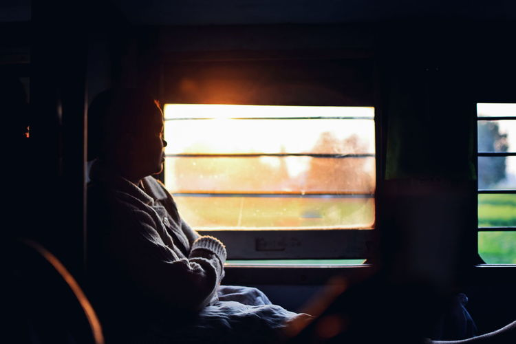 Side view of woman with arms crossed looking through window while traveling in train