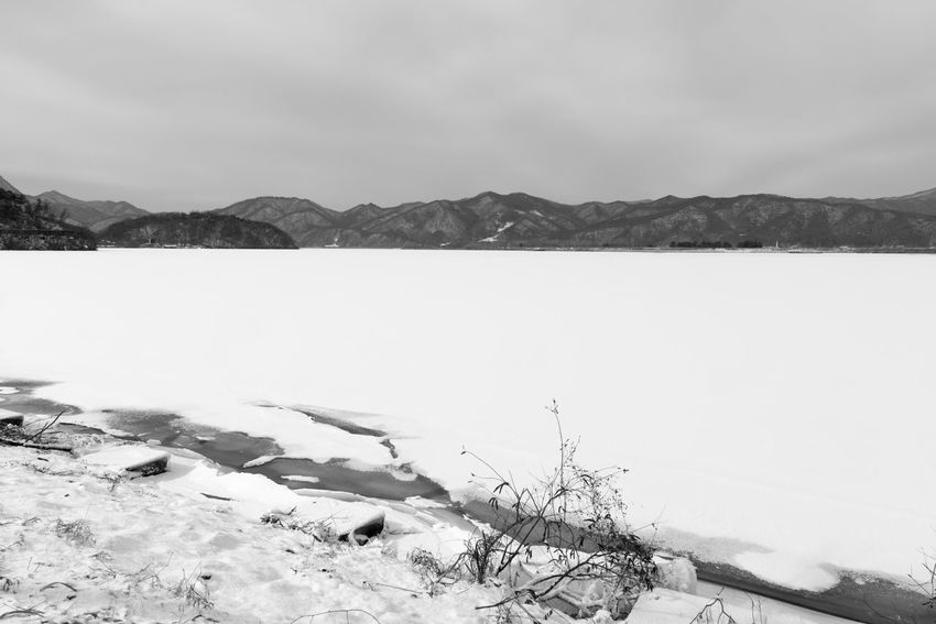 black and white image of snow-covered lake, Uiamho Lake in Chuncheon, Gangwondo, South Korea Black & White ChunCheon Cold Lake Cold Weather Gongjicheon Snow Land Uiamho Lake Winter Winter Landscape Beauty In Nature Black And White Blackandwhite Bw Cold Cold Temperature Day Ice Lake Landscape Mountain Mountain Range Nature No People Outdoors Scenics Sky Snow Snow-covered Snow-covered Lake Tranquil Scene Tranquility Travel Destinations Water Wilderness Area Winter Winter Lake Winter Land Winter Time