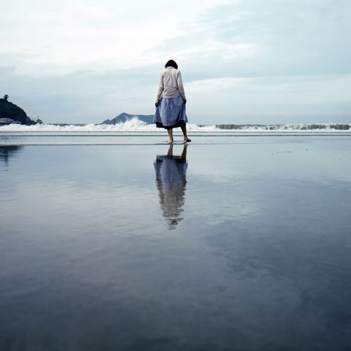 Rear View Of Woman On Shore At Beach Against Sky