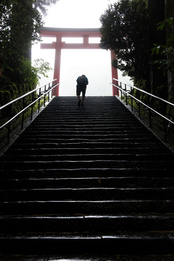 A pilgrim climbs the steep stone steps towards the brightly lit sky where a Shinto shrine sits, its approach marked by the traditional Japanese torii gate Ascending Bright Light Climb Japan Japanese Culture Shinto Shrine Shrine Silhouette Stairs Steps Stone Steps TORII Torii Gate Ascent Challenge Culture Glinting Sunlight Pilgrimage Religion Temple Inner Power
