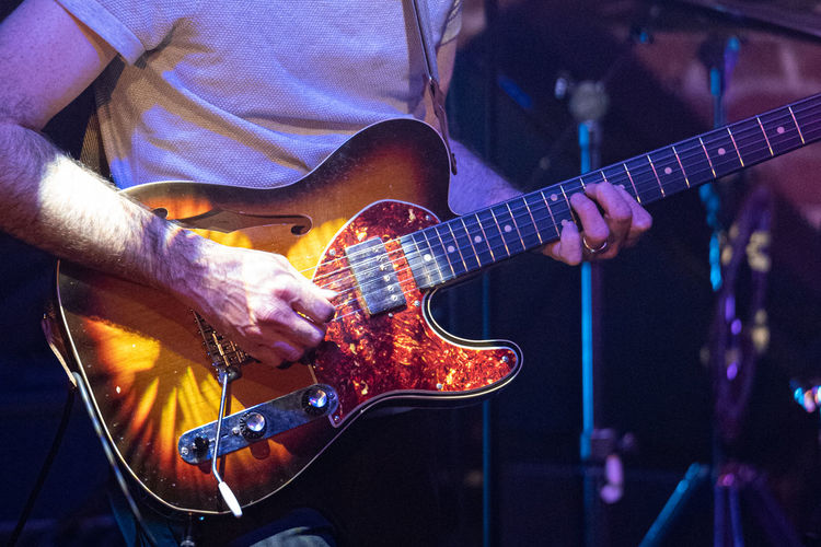 Midsection of man playing guitar at music concert