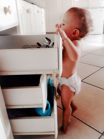 Full Length Of Baby Girl Standing By Drawers On Floor At Home