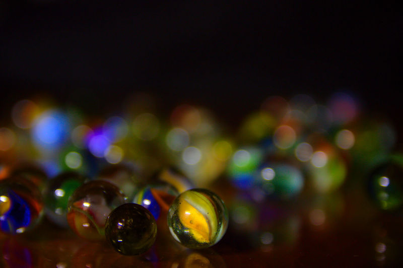 Black background, round bokeh and marbles on the table Canicas Group Of Objects Marbles Blurred Circle Colors Shadows & Lights Abstract Bokeh Boliche Close-up Colorful Defocused Explotion Of Color Focus On Foreground Illuminated Indoors  Macro Marbles Multi Colored Multi Colored Sky Night No People Reflections Shiny
