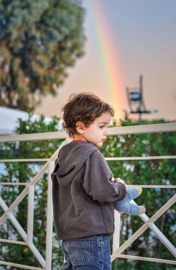 Cute Boy Standing By Railing Against Rainbow