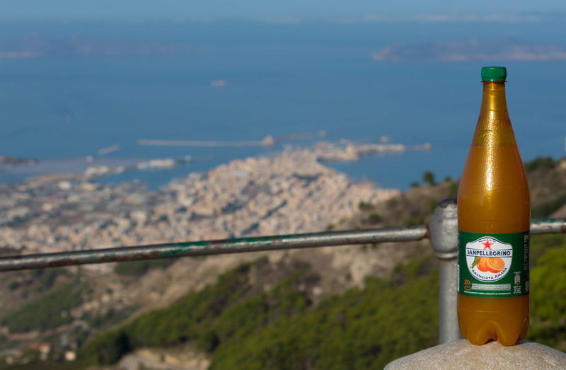 Low angle view of bottle by railing against sky