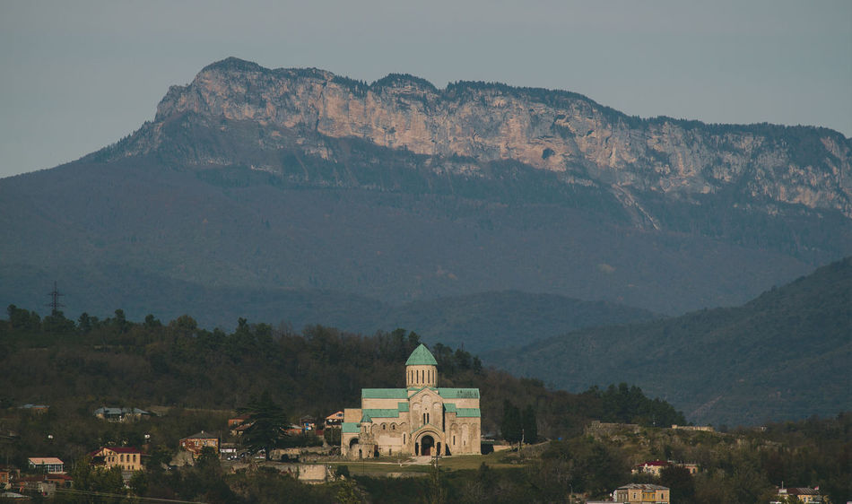 Bagrati catedral Mountain Architecture Built Structure Building Exterior Mountain Range Building Sky Nature No People Day Scenics - Nature Travel Destinations Beauty In Nature Religion Travel Tree History Residential District The Past Outdoors