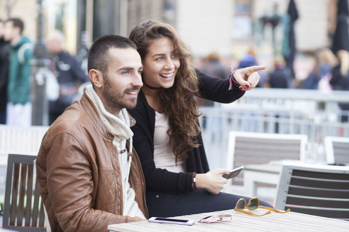 Young couple in love Shallow depth of field Adult Adults Only Beard Beautiful People Business Finance And Industry Cheerful City City Life City Street Coffee - Drink Couple - Relationship Happiness Heterosexual Couple Lifestyles Men Mid Adult People Portrait Smiling Table Togetherness Two People Wireless Technology Women Young Women