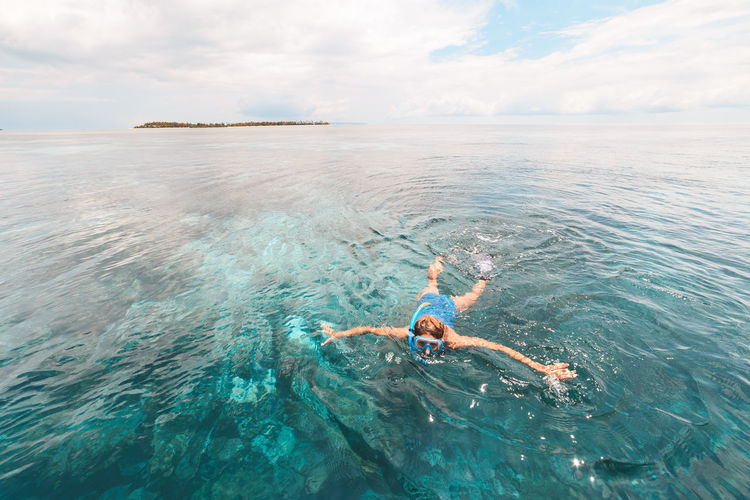 Woman snorkeling in sea against cloudy sky