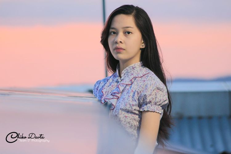 Beautiful young woman standing against sky during sunset