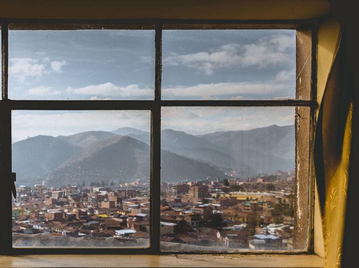 Cityscape against mountains seen through window