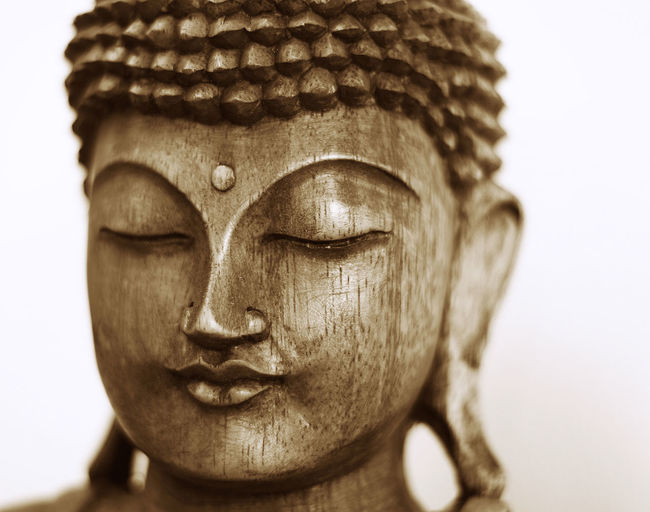 Close-up of buddha statue against white background