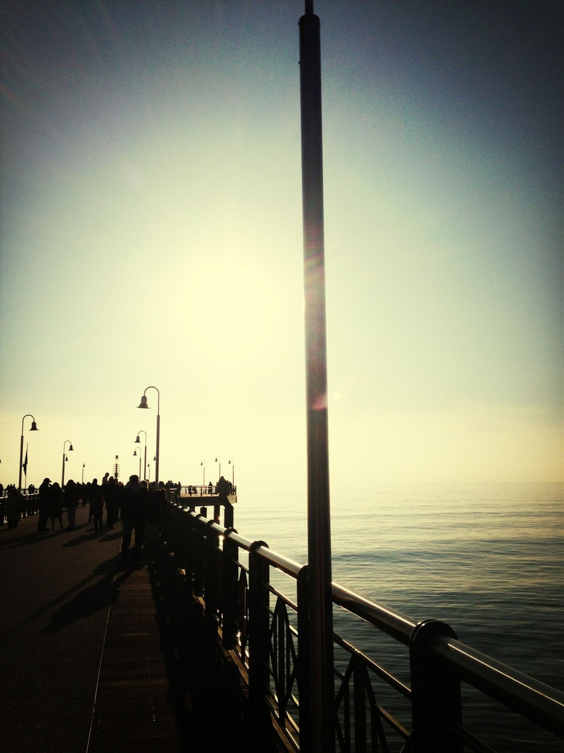 water, sea, railing, pier, the way forward, horizon over water, sunset, built structure, sky, street light, tranquility, nature, tranquil scene, scenics, silhouette, connection, beauty in nature, clear sky, long, architecture