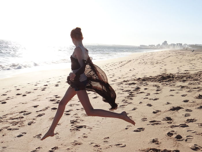 Full length side view of young woman jumping at beach on sunny day