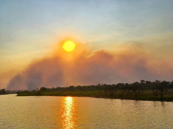 Sunset through the smoke of a bushfire on the banks of Hardie Billabong in the Northern Territory of Australia. Sunset Water Scenics Beauty In Nature Nature No People Outdoors Sun Sunlight Bushfire Global Warming Hardie Billabong Billabong Northern Territory Australia The Great Outdoors - 2017 EyeEm Awards