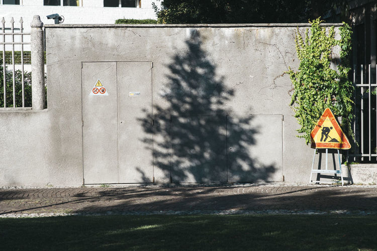 Architecture Built Structure Communication Day No People Outdoors Road Sign Shadow Sunlight Tree