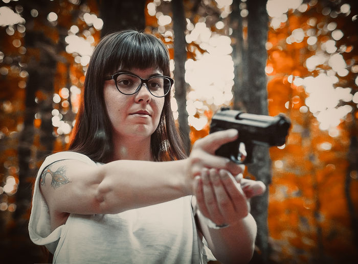 Woman shooting with handgun against trees in forest
