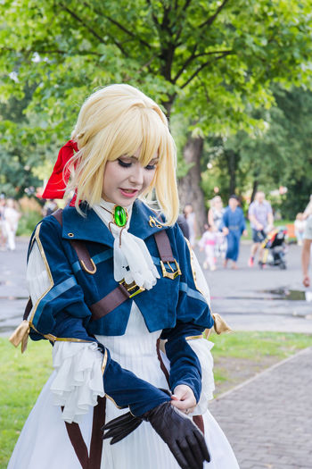Cosplay Adult Beautiful Woman Blond Hair Clothing Day Focus On Foreground Front View Hair Hairstyle Incidental People Leisure Activity Lifestyles Looking At Camera One Person Outdoors Real People Smiling Teenager Three Quarter Length Women Young Adult Young Women