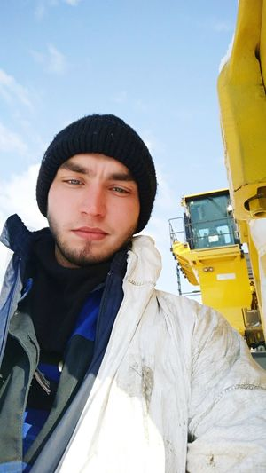Close-up portrait of young man against construction vehicle