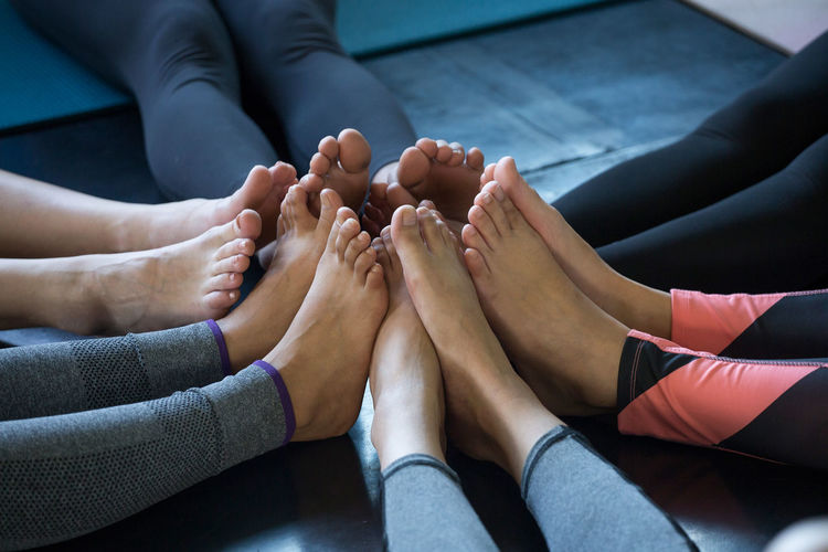Low section of friends joining legs on floor