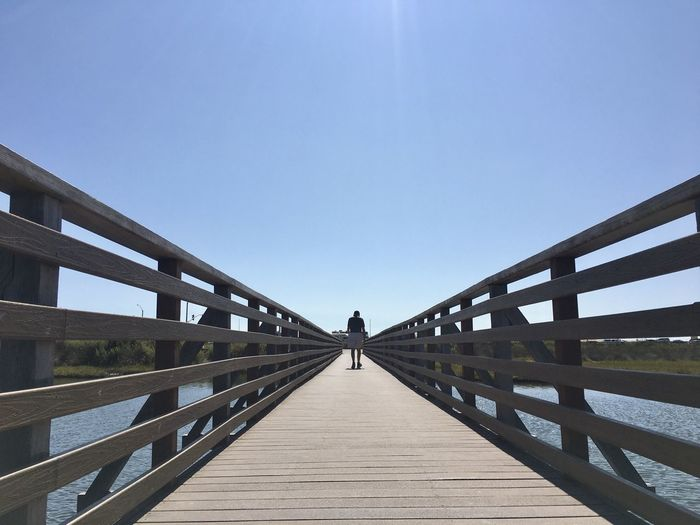 Full length of man walking on pier against sky