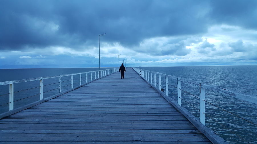 Rear View Of Man On Jetty Against Sea