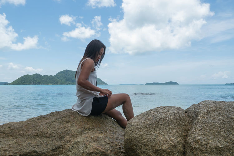 Young woman sitting on rock at sea shore against sky