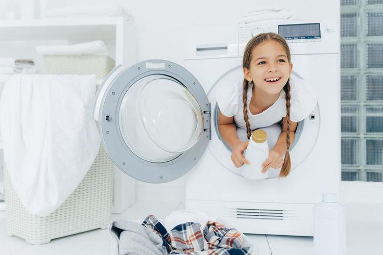 Smiling girl in washing machine at home