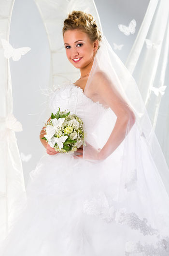 Beautiful cheerful bride indoors Summer Collection Summertime Beautiful Woman Blond Hair Bouquet Bridal Bridal Bouquet Bride Bunch Of Flowers Butterfly Female Flowers Life Events Marriage  One Person Smile Studio Shot Summer Veil Wedding Wedding Dress Weding Women Young Adult Young Women
