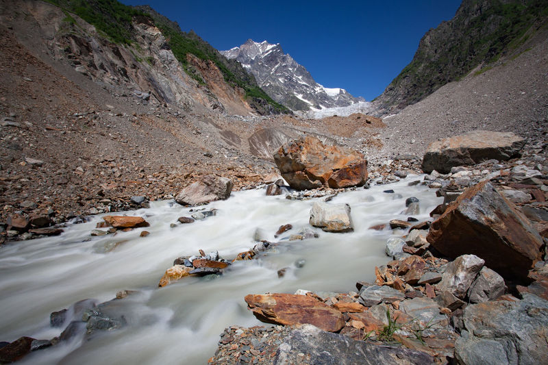 Scenic view of stream flowing through rocks against sky