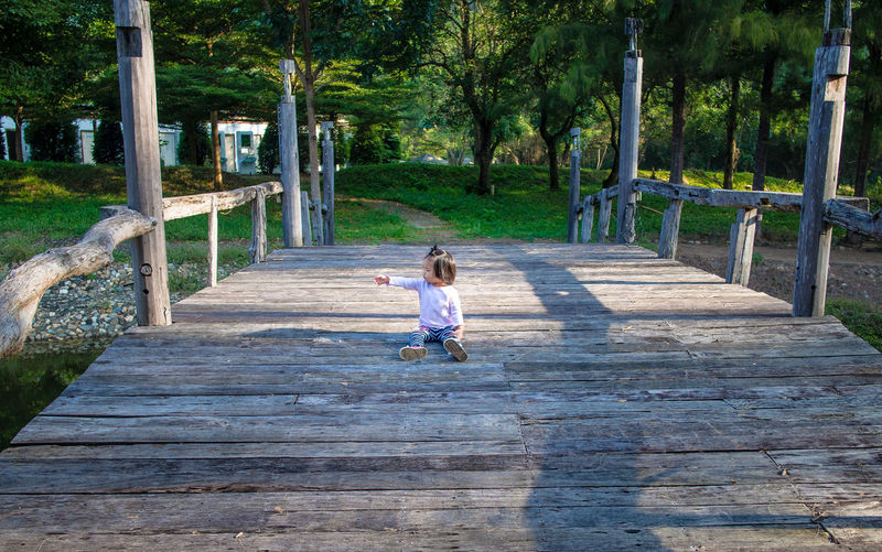 child girl sitting and finger pointing on the wooden bridge Wooden Bridge Asian Girl Casual Clothing Child Childhood Day Direction Females Finger Pointing Footpath Full Length Girls Innocence Nature One Person Outdoors Plant Rear View Staircase The Way Forward Tree Walking Wood - Material