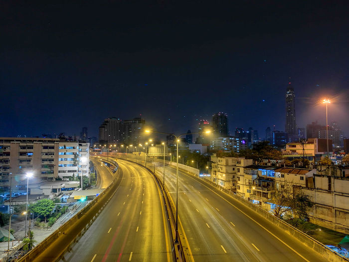 High angle view of light trails on road amidst buildings in city at night