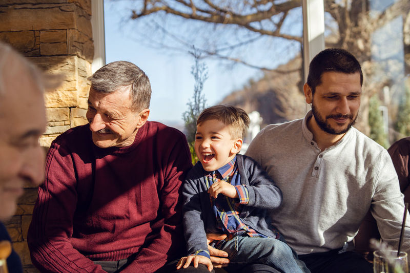 Grandparents looking at son talking to grandson at home