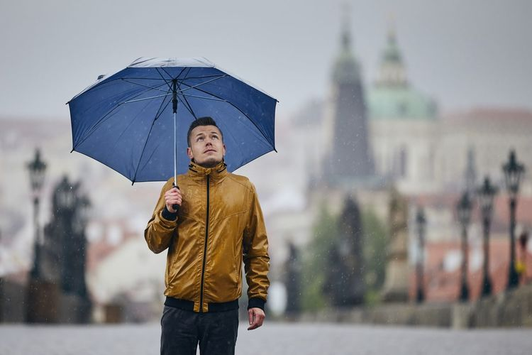 Man with umbrella standing in city during rainy season