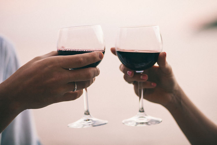 Close-up of hands holding wineglasses