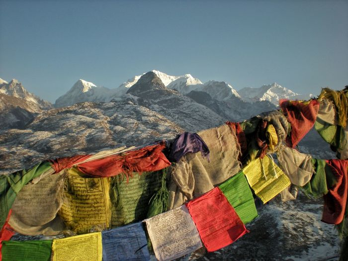 Prayer Flags Hanging Over Mountain Against Sky During Winter