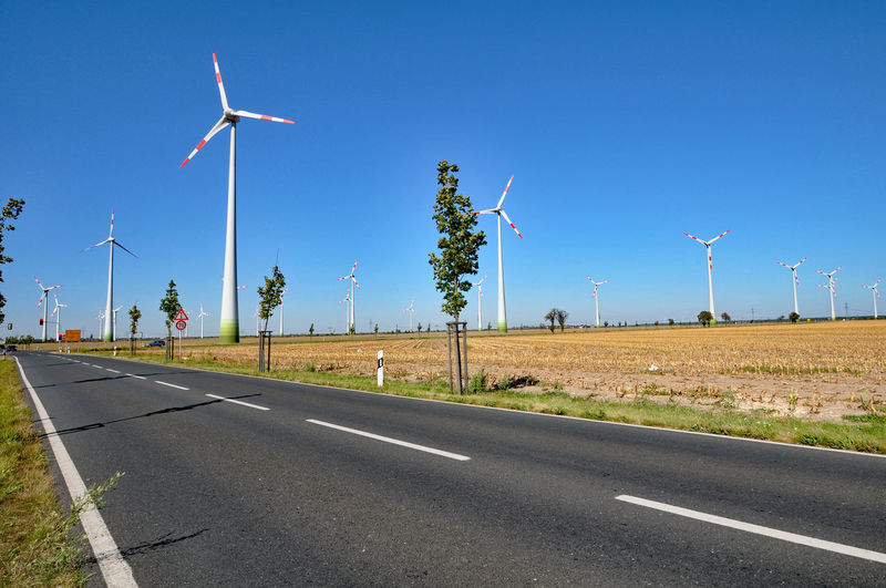 Windmills by empty road against clear blue sky