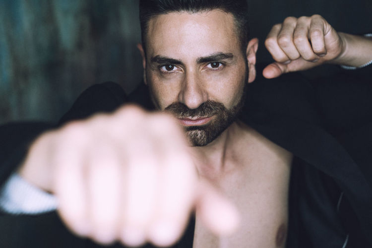 Portrait of bearded man clenching fist
