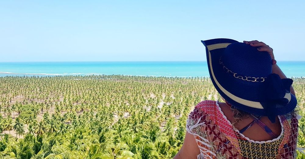 Woman wearing hat against sea against clear sky
