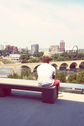 Man One Person Stone Arch Bridge Bridge - Man Made Structure River Riverside Rock Water Building Building Structures Bridge Walk City Sitting Rear View Sky Architecture Building Exterior Residential Structure Traditional Clothing Cityscape Skyline Skyscraper Tall - High Downtown Tower