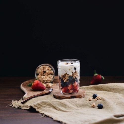 Muesli In Jar On Table Against Black Background