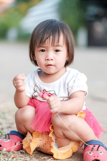 Portrait of cute baby girl sitting outdoors