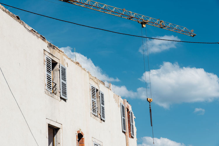 Low angle view of demolition building against sky. a crane demolishing a building