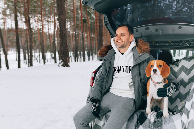 Smiling man with dog sitting in car trunk during forest