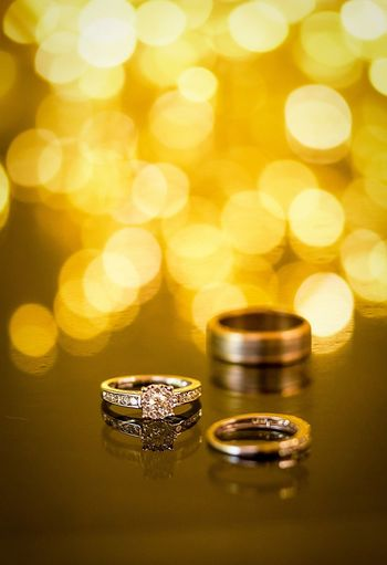 Close-up of wedding rings on table against lens flare