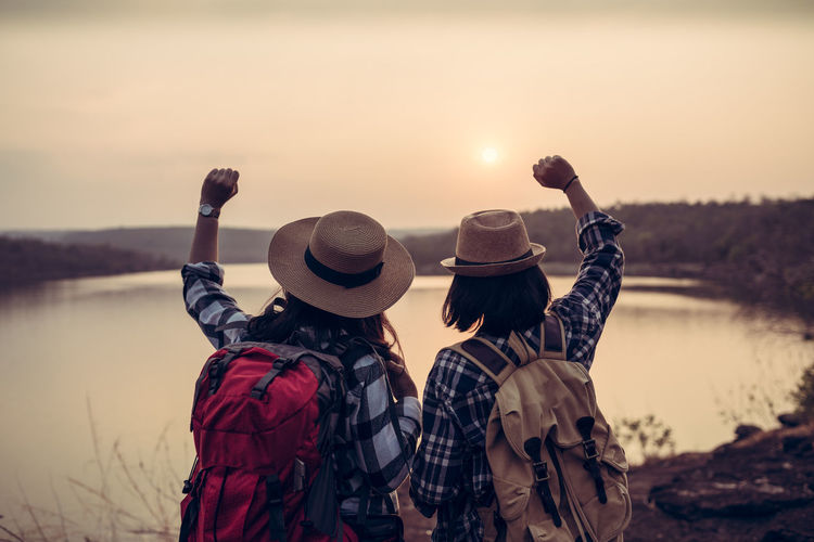 Successful trekking of two women and happiness in holiday Hat Sunset Sky Clothing Real People Water Lifestyles Nature Friendship Lake Adult Scenics - Nature Togetherness Rear View Leisure Activity Women Beauty In Nature Focus On Foreground People Outdoors Sun Portrait Hipster Backpack Friends Exploring Fun